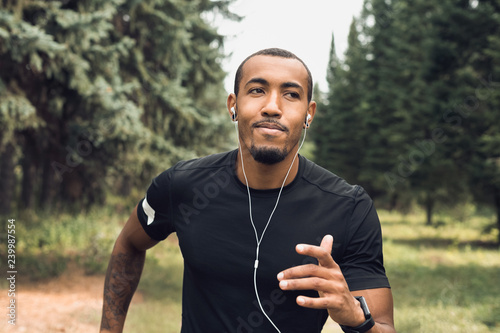 Fotografía  African-american man jogging and listening music outdoors