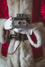 Midsection Of Santa Claus Holding Camera