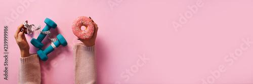 Foto  Female hand holding sweet donut, measuring tape, dumbbells over pink background