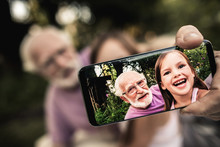 Grandfather With Grandchild Taking Picture Of Themselves