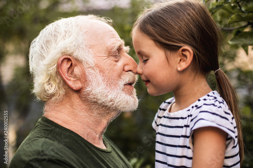 Fotografia  Little girl and her grandfather touch each other with their noses