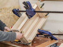Gluing The Wooden Box, Clamping With Clamps. Work In The Carpentry Workshop. Wooden Crafts. Fastening Parts.