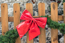 Christmas Red Bow On A Wooden Fence.