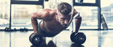 handsome shirtless sportsman training with dumbbells and doing plank in gym