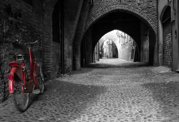 Das knallrote Fahrrad vor dunklen Torbögen