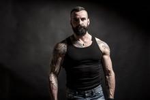 Uomo Muscoloso E Tatuato  Con Canottiera Nera E Jeans Su Sfondo Nero