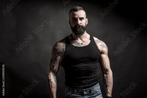 Fotografija  Uomo muscoloso e tatuato  con canottiera nera e jeans su sfondo nero