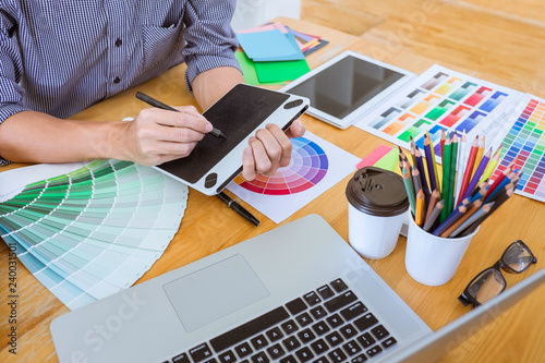 Young creative graphic designer working on project architectural drawing and color swatches, selection coloring on graphic chart with work tools and equipment