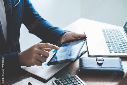 Canvastavla Businessman hand using digital tablet to analyze financial statistical data