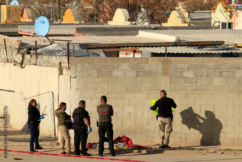 Forensic technicians work at a crime scene where a beheaded