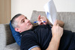 A man looks through business documents, reports. Malaise, work in home environment.