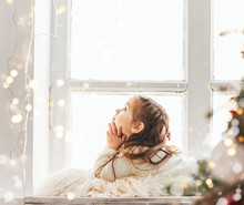 Cute Little Girl Laying On Windowsill On Christmas. Bright Happy Christmas Picture.
