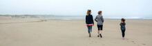 Back View Of Three Generations Female Walking On The Beach In Autumn