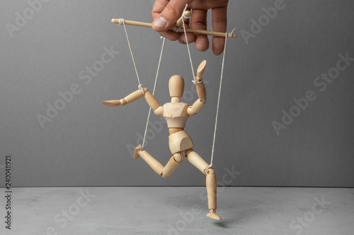 Fototapeta The puppeteer holds the doll by the rope