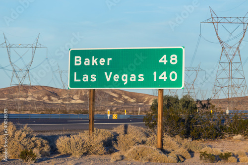 Late afternoon view of Las Vegas 140 miles and Baker 48 miles highway sign on I-15 near Barstow in California.
