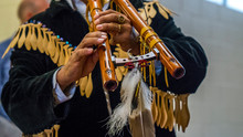 Close Up Of A Native American Indian Playint At Flute.