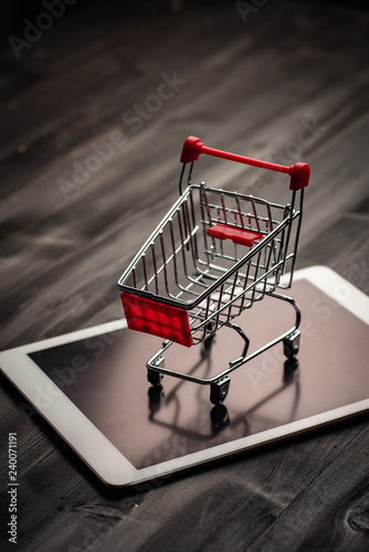 close-up of shopping trolley on tablet with darkwood background with some copy space,shopping online concept Fototapeta