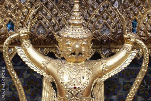 close up golden Garuda statue stand around , the bronze symbol of Thai government, giant ancient gold eagle with crown sculpture antique signature on temple royal palace wall
