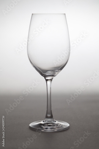Glass wine glass stands on gray background