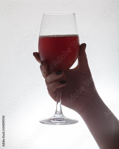 Hand holding  glass goblet with wine