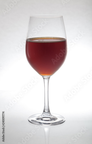 Glass goblet with wine stands on glass on  white background