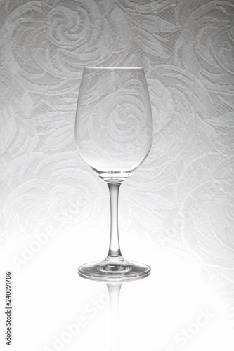 Glass wine glass stands on a blurred background
