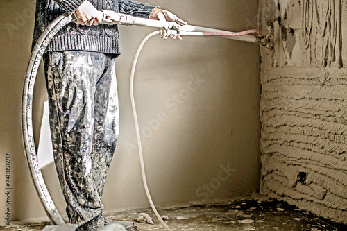 Fotografie, Obraz  Worker applying gypsum plaster to the aerated concrete wall with a spray plastering machine