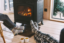 Cold Fall Or Winter Day. People Drinking Tea And Resting By The Stove. Closeup Photo Of Human Feet In Warm Woolen Socks Over Fire Place. Hygge Concept Of Cozy Winter Weekend In Cabin.