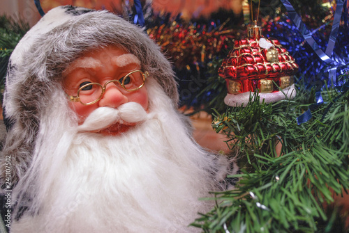 Acrylic Prints Roe Santa Claus with toy under the Christmas tree.