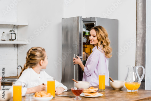 Leinwand Poster girl sitting at table and looking at mother opening fridge