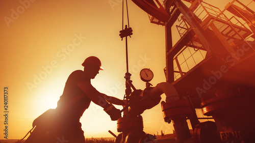 Fototapeta Oil worker is checking the oil pump on the sunset background. obraz
