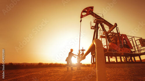 Fotografia  Oil worker is checking the pump near oil derrick on the sunset background