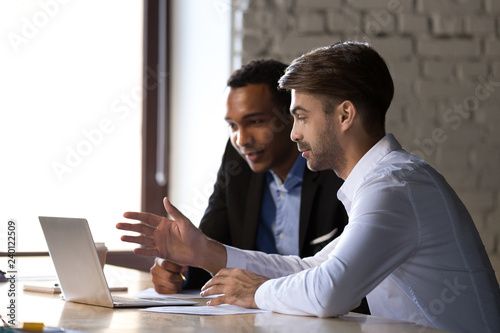 Foto  Financial advisor insurer speaking consulting african client looking at laptop m