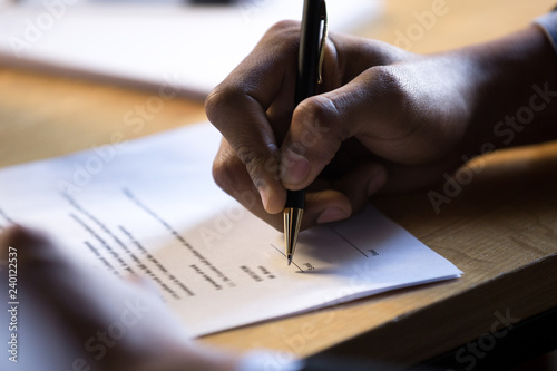Fotografie, Obraz  Male african hand signing financial contract concept, black businessman put writ