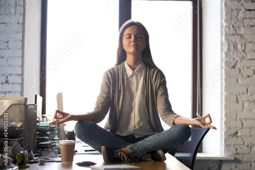 Fotografie, Obraz  Serene calm business woman sit on office desk taking break for meditation, mindf