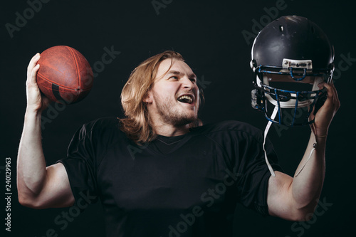 Confident caucasian american football player in black protective uniform looking at helmet with pleased expression, posing before game starts, being sure to win