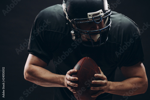 American football player with black helmet and armour running in motion, holding ball, getting ready to score a goal, close up shot over dark background