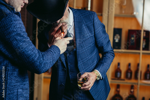 Foto  Elegant senior gentleman wearing spectacles and grey-haired beard standing at pub in wide-brimmed hat with glass of alcohol drink and cigar