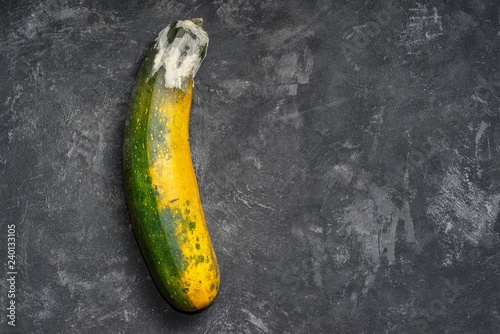 Moldy zucchini on a black cement textured background top view with copy space. Bad storage concept,