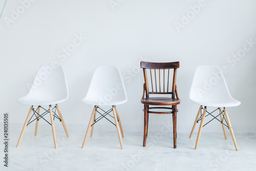 Modern style of three plastic chairs versus Vintage style of one brown wooden ch Wallpaper Mural