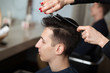 Hairdresser cutting man's hair with scissors. young man having new haircut in barber shop.