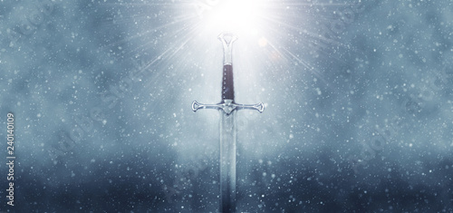 mysterious and magical photo of silver sword over gothic snowy black background. Medieval period concept.