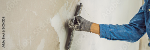 Fotografía  master is applying white putty on a wall and smearing by putty knife in a room o