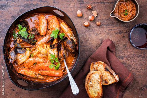 Traditional Catalan fish stew romesco de peix with prawns, mussels and fish as top view in a modern design cast-iron roasting dish