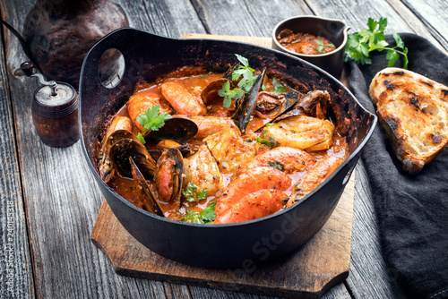 Traditional Catalan fish stew romesco de peix with prawns, mussels and fish as closeup in a modern design cast-iron roasting dish
