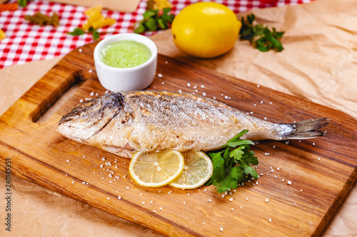 Fotografie, Obraz Grilled dorado fish with lemon and sauce on wooden board