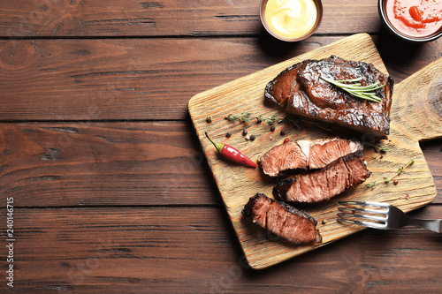 Flat lay composition with delicious barbecued meat on wooden background. Space for text