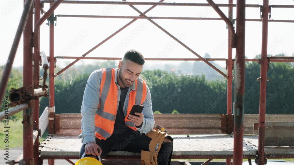 Fototapeta Man Working In Construction Site Smiling And Using Smartphone