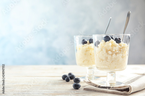 Creamy rice pudding with blueberries in dessert bowls on table. Space for text