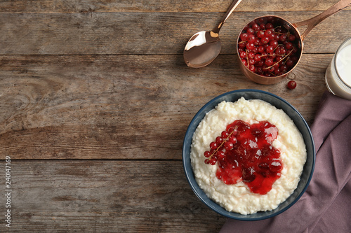Creamy rice pudding with red currant and jam in bowl served on wooden table, top view. Space for text